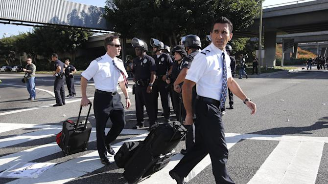 Two flight crew members walk past Los Angeles police officers as union workers at Los Angeles International Airport march along the street in Los Angeles, Wednesday, Nov. 21, 2012. Hundreds of union members marched Wednesday near the entrance to Los Angeles International Airport, where Thanksgiving travelers were warned to arrive early in case of traffic snarls. (AP Photo/Jae C. Hong)