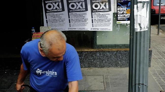 A man searches in a bin in front of a posters for the NO vote in the upcoming referendum, in central Athens Tuesday, June 30, 2015. Greek Finance Minister Yanis Varoufakis confirmed that the country will not make its payment due later to the International Monetary Fund. Capital controls began Monday and will last at least a week, an attempt to keep the banks from collapsing in the face of a nationwide bank run. (AP Photo/Petros Karadjias)