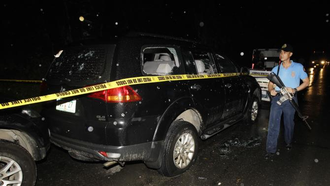 Police pass by the bullet-riddled vehicle of suspected criminals along a road in the town of Atimonan in Quezon province, about 140 kilometers (100 miles) southeast of Manila, Philippines late Sunday Jan. 7, 2013. Philippine army special forces and police killed 13 suspected criminals in a gunbattle Sunday in the latest violence to erupt in the country in the past week. (AP Photo/Aaron Favila)
