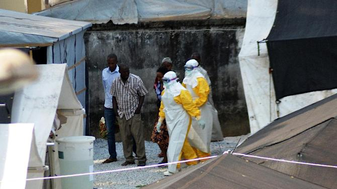 Health workers wearing protective suits walk in an isolation center for people infected with Ebola at Donka Hospital in Conakry on April 14, 2014