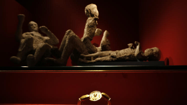 Jewellery found in the ruins of a house in Pompeii are displayed, backdropped by the casts of a family of two adults and two children who died together in the house in Pompeii, are seen during a photo call for the upcoming exhibition entitled 'Life and death Pompeii and Herculaneum', at the British Museum in central London, Tuesday, March 26, 2013. The casts were made by filling plaster in the void left by their bodies. The exhibition about the two Roman cities, buried by a catastrophic volcanic eruption of Mount Vezuvius in 79 AD, will run at the museum from March 28 to Sept. 29, 2013. (AP Photo/Lefteris Pitarakis)