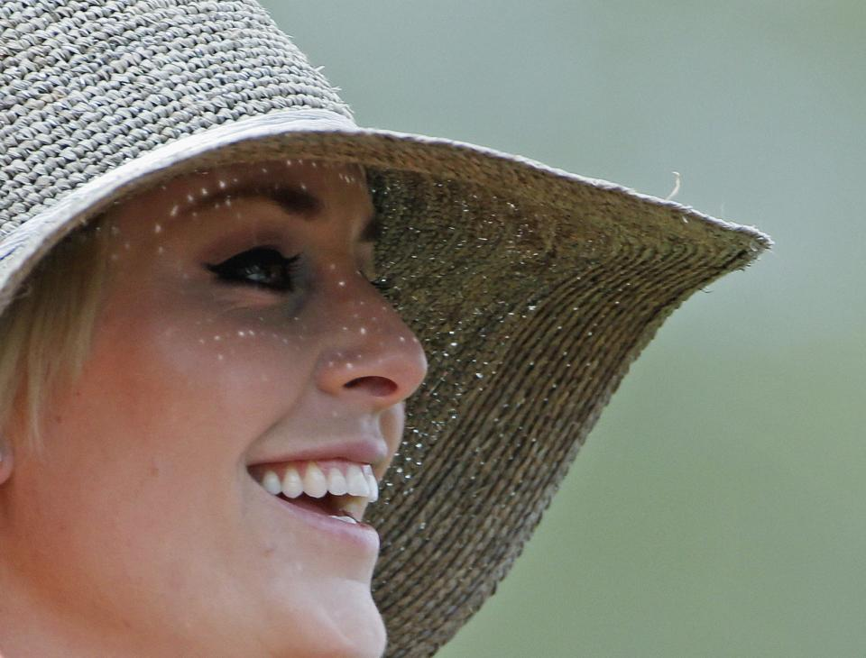 Skier Lindsey Vonn smiles as she watches Tiger Woods during the first round of the Masters golf tournament Thursday, April 11, 2013, in Augusta, Ga. (AP Photo/Darron Cummings)