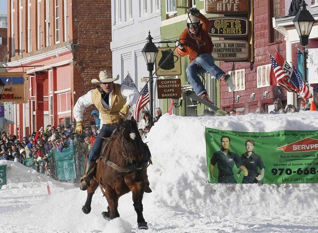 A horseman pulls a skier down the snow-covered main street during the annual skijoring race in downtown Leadville, Colorado