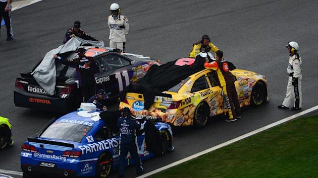 Crew members of NASCAR Sprint Cup Series driver Denny Hamlin (11), Kyle Busch (18) and Kasey Kahne (5) put covers over the cars during a rain delay during the Daytona 500 (Reuters)
