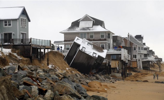 A house on Plum Island sits on its side after coming off its foundation in the high tide during an overnight winter storm in Newbury