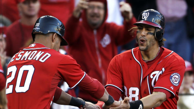 Washington Nationals' Ian Desmond, left, and Michael Morse celebrate after scoring on a two-RBI single by Tyler Moore during the eighth inning in Game 1 of baseball's National League division series against the St. Louis Cardinals, Sunday, Oct. 7, 2012, in St. Louis. (AP Photo/Jeff Roberson)