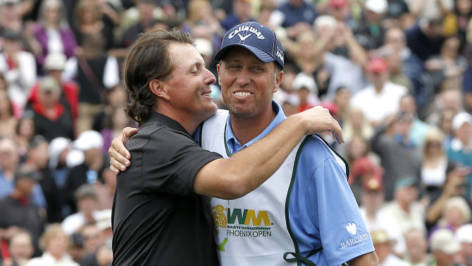 Phil Mickelson, left, hugs his caddie, Jim Mackay, after winning the Waste Management Phoenix Open golf tournament on Sunday, Feb. 3, 2013, in Scottsdale, Ariz. (AP Photo/Matt York)