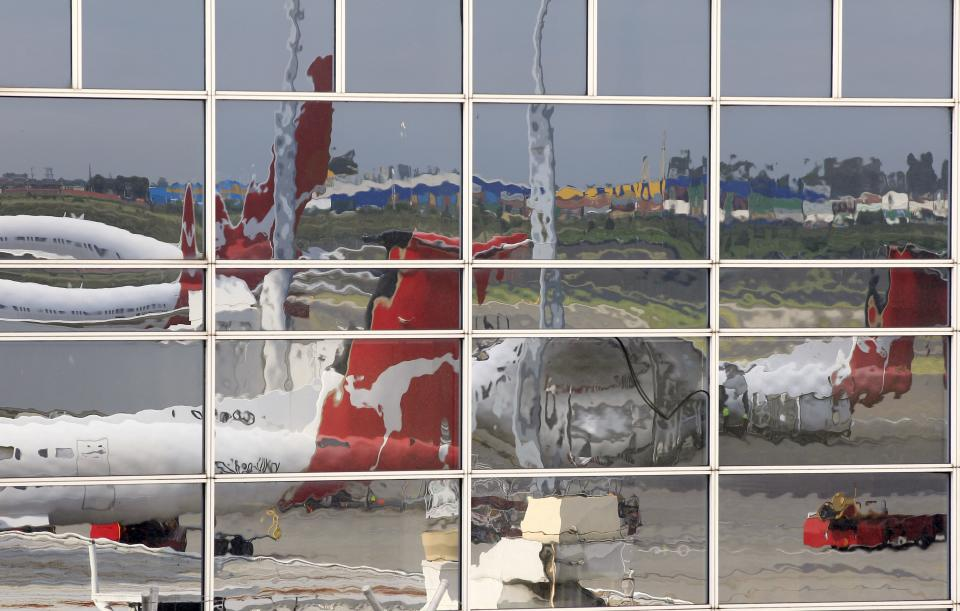 Idle Qantas planes are reflected in a window at Sydney Airport in Sydney, Sunday, Oct. 30, 2011. Qantas Airways grounded all of its aircraft around the world indefinitely Saturday due to ongoing strikes by its workers. (AP Photo/Rick Rycroft)