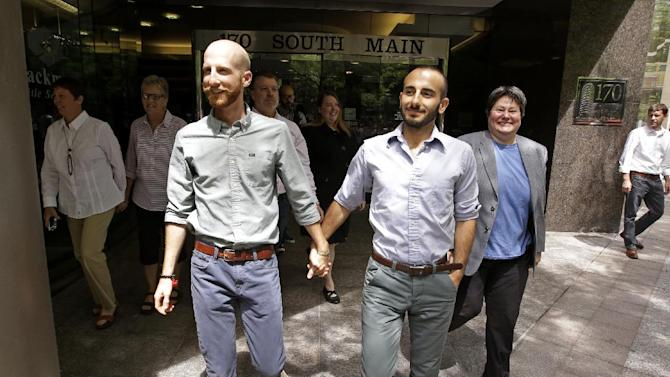 FILE - In this June 25, 2014, file photo, plaintiffs Moudi Sbeity, right, and his partner Derek Kitchen, one of three couples who brought the lawsuit against Utah's gay marriage ban, walk with other plaintiffs after arriving for a news conference in Salt Lake City. The 10th Circuit Court of Appeals in Denver ruled on June 25 that Utah must allow gay couples to marry, finding the Constitution protects same-sex relationships. The court made the same ruling on Oklahoma's ban Friday. Utah and Oklahoma voters overwhelmingly passed the bans in 2004. (AP Photo/Rick Bowmer, File)