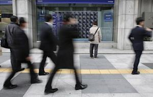 Man looks at a stock quotation board as passers-by walk past, outside a brokerage in Tokyo