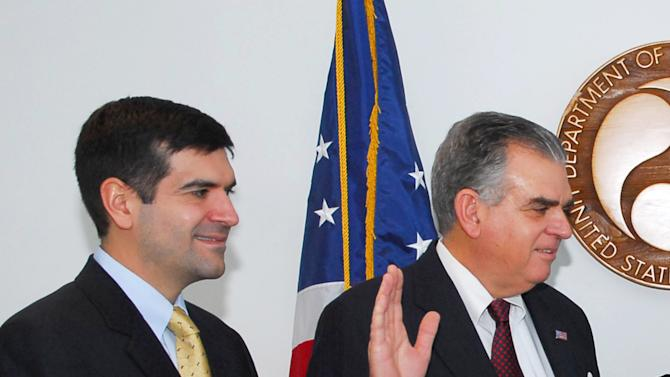 FILE - In this Jan. 23, 2009, photo released by the Transportation Department, Sam LaHood, left, watches as his father Ray is sworn in as Transportation Secretary, at the Transportation Department in Washington. Two months before Egyptian police stormed the offices of U.S.-backed democracy organizations in 2011, 7 Egyptian employees resigned from one of the American groups to protest what they called very undemocratic practices. This wasn't the democracy that Dawlat Soulam, one of those who quit, said she had hoped to deliver to Egypt when she went to work for the International Republican Institute. Soulam, a New York City-born Egyptian with dual citizenship, and the others said they were troubled by work being done under the programs run by Sam LaHood. Interviews and documents obtained by The Associated Press show that the workers' protest and the broader government crackdown with the raids helped expose what U.S. officials do not want to admit publicly: the American government spent tens of millions of dollars financing and training liberal groups in Egypt, the backbone of the Egyptian uprising. This was done to build opposition to Islamic and pro-military parties in power - all in the name of democracy development. And, all while American diplomats were assuring Egyptian leaders the U.S. was not taking sides. (AP Photo/Transportation Department)