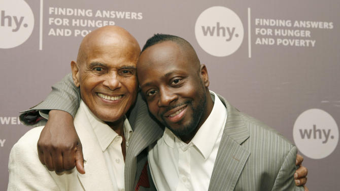 """FILE - In this June 8, 2009, file photo provided by WHY (World Hunger Year), Grammy Award winning musician Wyclef Jean, right, puts his arm around Harry Belafonte, left, before being presented with the ASCAP- Harry Chapin Humanitarian Award at WHY's annual gala in New York. Chapin has been gone now nearly as long as he lived. WhyHunger is a charity Chapin co-founded as ''World Hunger Year"""" in the 1970s.  Belafonte, a previous recipient of the award, said Belafonte says Chapin's social conscience came through not only in the lyrics of his songs, but in his actions offstage. (AP Photo/Stuart Ramson, WHY, File)"""