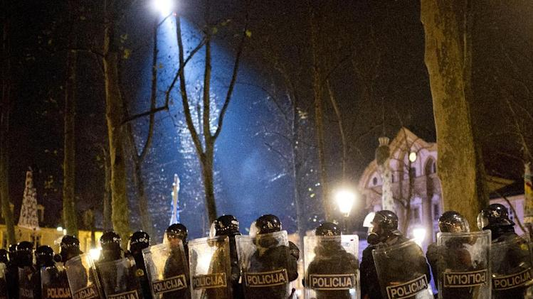 A police helicopter casts light on riot police as they secure the area near the parliament building in Ljubljana, Slovenia, Friday, Nov. 30, 2012.  Thousands joined anti-government protests in Slovenia on Friday as tensions soared ahead of this weekend's presidential runoff in the small, economically struggling EU nation. (AP Photo/Matej Leskovsek)