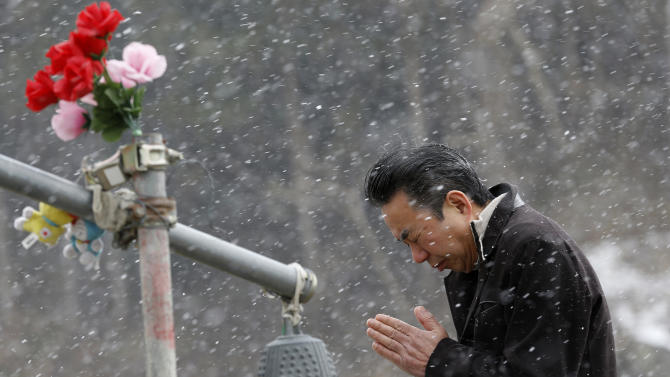 A man offers prayers in front of the main entrance of Okawa Elementary School where 74 of the 108 students went missing after the March 11, 2011 tsunami in Ishinomaki, Miyagi prefecture, northern Japan, Tuesday, March 11, 2014. Japan on Tuesday marks the third anniversary of the March 11, 2011 earthquake and tsunami that killed 15,884 people and left more than 2,600 unaccounted for in vast areas of its northern coast. (AP Photo/Shizuo Kambayashi)