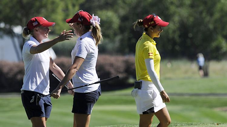 Stacy Wright, left, and Paula Creamer celebrate on the 18th hole as Azahara Munoz, right, of Spain, walks off the green during the second round of the International Crown golf tournament Friday, July 25, 2014, in Owings Mills, Md. (AP Photo/Gail Burton)