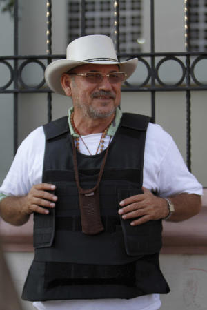 "FILE - In this Feb. 9, 2014 file photo, Hipolito Mora, leader of a self-defense movement, wears a bullet proof vest as he stands at the entrance of Apatzingan, in the Michoacan state of Mexico. Self-defense groups in western Mexico are beginning to see internal divisions, amid mutual accusations between Mora and another emerging leader, Luis Antonio Torres, better known as ""El Americano,"" who has accused Mora of being involved in the murder of a member of their vigilantes during the weekend. Mora, meanwhile, rejects the accusations and says that ""El Americano"" has been infiltrated by former members of the ""Caballeros Templarios"" drug cartel. (AP Photo/Marco Ugarte, File)"