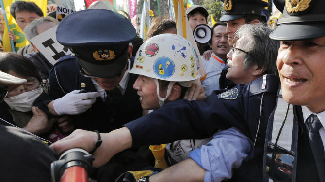 A protester struggles with a police officer during a rally against nuclear power plants at a park in Tokyo, Saturday, March 9, 2013. Thousands of people rallied in a Tokyo park Saturday, demanding an end to atomic power, and vowing never to give up the fight, despite two years of little change after the nuclear disaster in Fukushima, northeastern Japan. (AP Photo/Itsuo  Inouye)