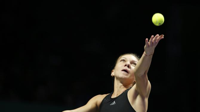 Simona Halep of Romania serves against Serena Williams of the U.S. during their WTA Finals singles tennis match at the Singapore Indoor Stadium