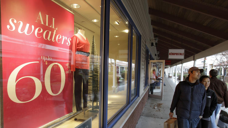 In this Dec. 1, 2010 photo, holiday shoppers walk around the Wrentham Premium Outlet mall in Wrentham, Mass. (AP Photo/Stephan Savoia)