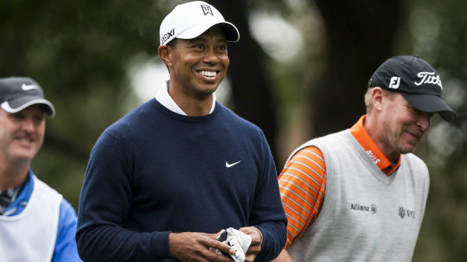 Tiger Woods, center, and Steve Stricker laugh after teeing off on the sixth hole during the first round of the World Challenge golf tournament at Sherwood Country Club in Thousand Oaks, Calif., Thursday, Nov. 29, 2012. (AP Photo/Bret Hartman)
