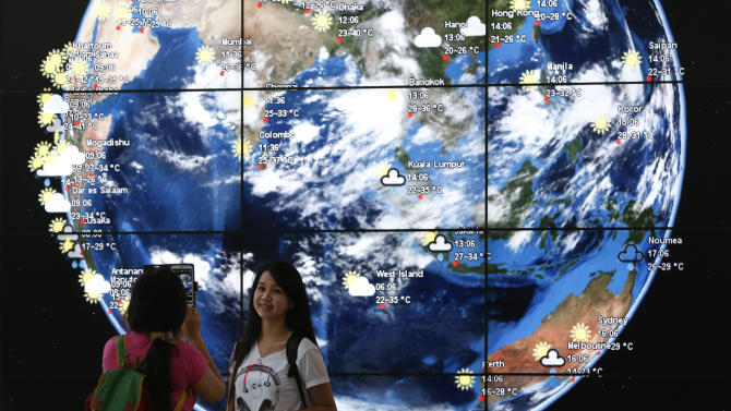 A Chinese girl is taken a picture in front of an electronic display showing the weather information of the cities in Asia at the Kuala Lumpur International Airport, in Sepang, Malaysia, Monday, March 17, 2014. When someone at the controls calmly said the last words heard from the missing Malaysian jetliner, one of the Boeing 777's communications systems had already been disabled, adding to suspicions that one or both of the pilots were involved in the disappearance of the flight. (AP Photo/Vincent Thian)