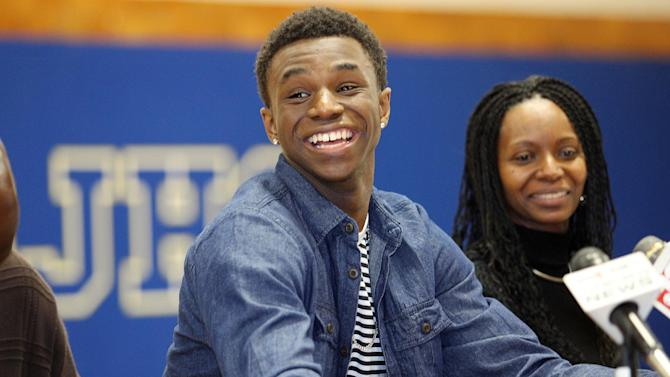 Huntington Prep basketball player Andrew Wiggins smiles along side his mother Marita Payne-Wiggins, right, as he announces his commitment to the University of Kansas during a ceremony, Tuesday, May 14, 2013, at St. Joseph High School in Huntington W.Va. The Canadian star, a top prospect, averaged 23.4 points and 11.2 rebounds per game this season for West Virginia's Huntington Prep. (AP Photo/The Herald-Dispatch, Sholten Singer)