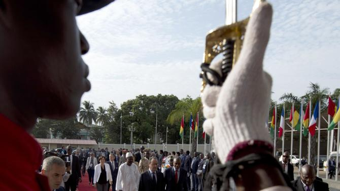 French president Hollande walks with Guinea's President Alpha Omar Conde, at the Nations Palace in Conakry