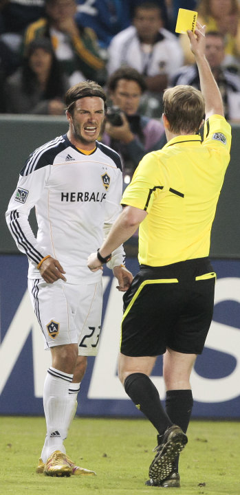 Los Angeles Galaxy midfielder David Beckham, left, reacts after receiving a yellow card during the second half of an MLS soccer match against the Columbus Crew, Wednesday, July 20, 2011, in Carson, Ca