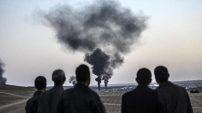 People watch as smokes rises from the town of Kobane, also known as Ain al-Arab, on October 26, 2014, at the Turkish border near the southeastern village of Mursitpinar
