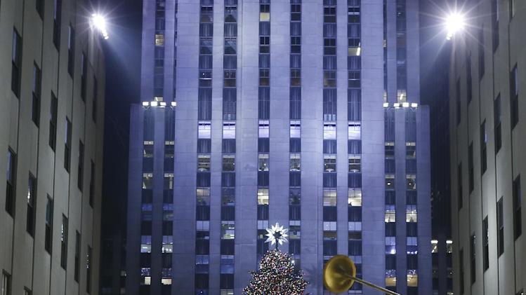 The Rockefeller Center Christmas tree is shown surrounded by angels in a view from the Channel Gardens, Wednesday, Dec. 4, 2013, in New York. Some 45,000 energy efficient LED lights adorn the 76-foot tree. (AP Photo/Kathy Willens)