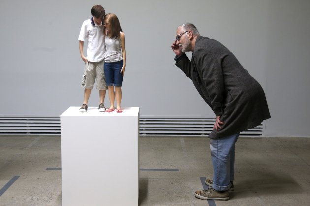 "A visitor looks at a sculpture entitled ""Young Couple, 2013"" by artist Ron Mueck during his exhibition at the Fondation Cartier pour l'art contemporain in Paris"
