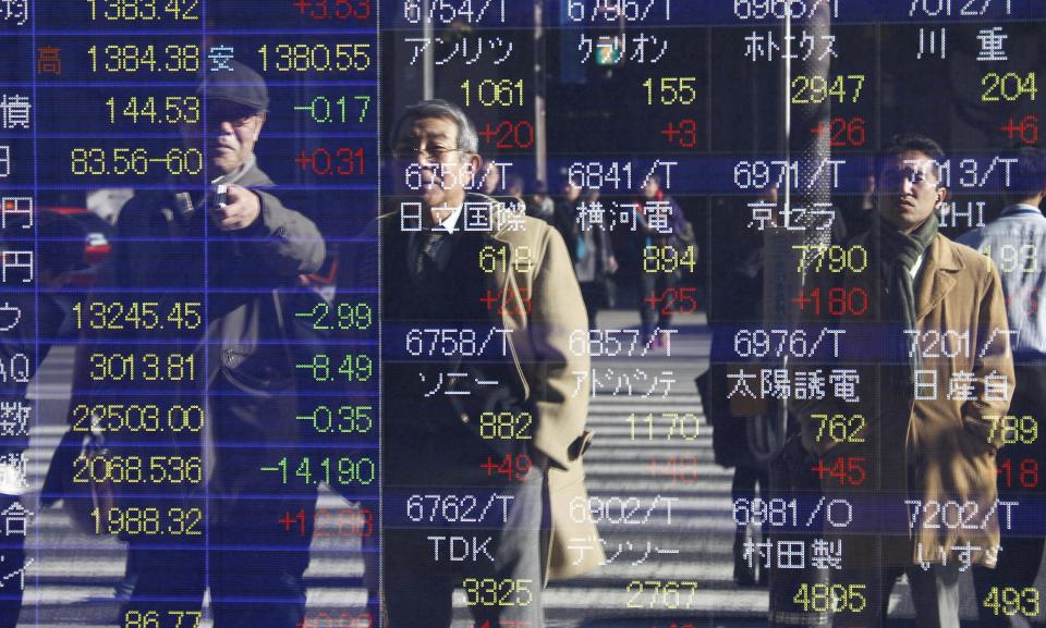 People are reflected on the electronic board of a securities firm in Tokyo Thursday, Dec. 13, 2012. Asian stock markets rose Thursday with the help of Japan's Nikkei 225, which was propelled higher by a weakening yen. (AP Photo/Koji Sasahara)