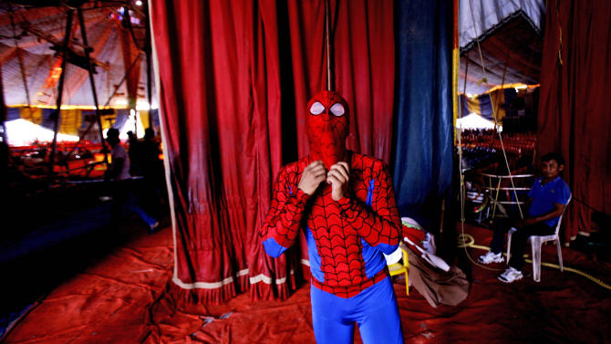 In this April 11, 2013 photo, a circus artist wears a Spiderman costume before a performance at the Rambo Circus on the outskirts of Mumbai, India. Circuses around the world may struggle to compete with an ever-increasing array of entertainment options, but India's once-widespread industry in particular has gone through cataclysmic changes. In the 1990s, there were 300 circuses operating throughout the country. That number has now dwindled to about 30, says circus manager John Matthew, and many of those are in financial trouble due to rising costs of renting field space, shrinking revenues and - crucially - two Supreme Court rulings that took away two of the industry's main attractions. (AP Photo/Rafiq Maqbool)