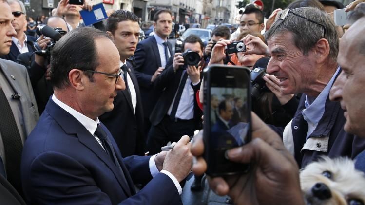 French President Francois Hollande signs autographs after a ceremony in front 'La Taverne du Croissant' Cafe in Paris for the 100th anniversary of the assassination of the Socialist leader Jaures