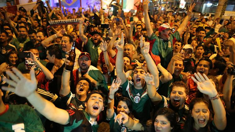 CORRECTS FINAL SCORE OF THE GAME - Mexico soccer fans celebrate a goal scored by their team on a street of Copacabana, in Rio de Janeiro, Brazil, Monday, June 23, 2014. Mexico defeated Croatia, by 3-1, and will play the next phase of the world tournament. (AP Photo/Leo Correa)
