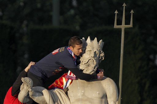Atletico de Madrid's Gabi Fernandez put a scarf in the neck of Neptuno, in Madrid, Spain, Saturday, May 18, 2013. Atletico de Madrid defeated Real Madrid in the Copa del Rey final soccer match on Frid
