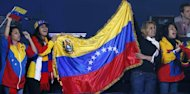 Fan from Venezuela cheer countryman Gabriel Maestre Perez  against Siphiwe Lusizi of South Africa during their round of 16 Welterweight (69kg) match of the London 2012 Olympic Games at the ExCel Arena on August 3, 2012 in London. Maestre Perez was awarded an 18-13 points decision. AFP PHOTO / Jack GUEZ