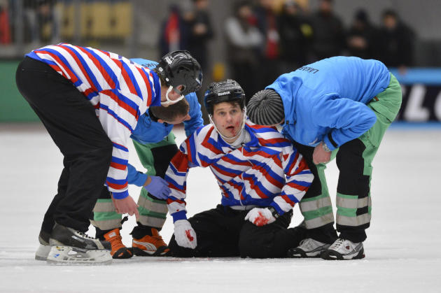 Injured referee Kuusela is helped off the ice during the final match between Sweden and Russia at the Bandy World Championship in Vanersborg