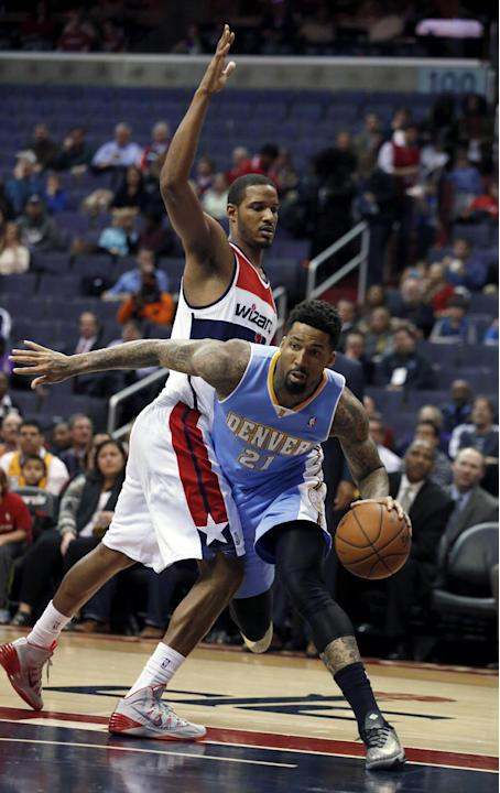 Denver Nuggets forward Wilson Chandler (21) drives around Washington Wizards forward Trevor Ariza, left, in the first half of an NBA basketball game on Monday, Dec. 9, 2013, in Washington