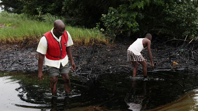FILE - In this June 20, 2010 file photo, men walk in an oil slick covering a creek near Bodo City in the oil-rich Niger Delta region of Nigeria. Shell officials on Monday, Sept. 9, 2013 began talks in Nigeria's southern city of Port Harcourt with representatives for the Bodo community on compensation and cleanup five years after one of the worst oil spills in Nigeria's history. (AP Photo/Sunday Alamba, File)