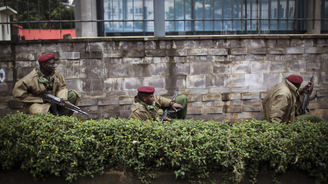 """Kenya security forces are seen behind a wall outside the Westgate Mall in Nairobi, Kenya Monday morning, Sept. 23, 2013. Kenya's military launched a major operation at the upscale Nairobi mall and said it had rescued """"most"""" of the hostages being held captive by al-Qaida-linked militants during the standoff that killed at least 68 people and injured 175. (AP Photo/Jerome Delay)"""