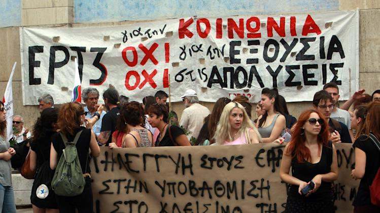 "Workers protest outside the Greek state television ERT 3 headquarters after the government's decision to shut down the broadcaster in Thessaloniki, on Thursday, June 12, 2013. State TV and radio signals were cut early Wednesday, hours after the government closed the Hellenic Broadcasting Corp., ERT, and fired its 2,500 workers. Banner reads ""No to the lay offs"" and ""solidarity to the workers"". (AP Photo/Nikolas Giakoumidis)"