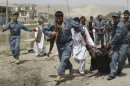 "Afghan policemen evacuate a wounded person after a suicide bomber struck outside a provincial council headquarters in Pul-i-Khumri, Baghlan province, northern Afghanistan, Monday, May 20, 2013, killing the council chief and at least more than a dozen others, authorities said. Afghan President Hamid Karzai condemned the bombing saying the killing of civilians shows the ""true nature"" of the Taliban, who seek to re-establish the strict interpretation of Islamic law they imposed for five years before being ousted in the 2001 U.S.-led invasion over its sheltering of al-Qaida's terrorist leadership. (AP Photo/Jawed Basharat)"