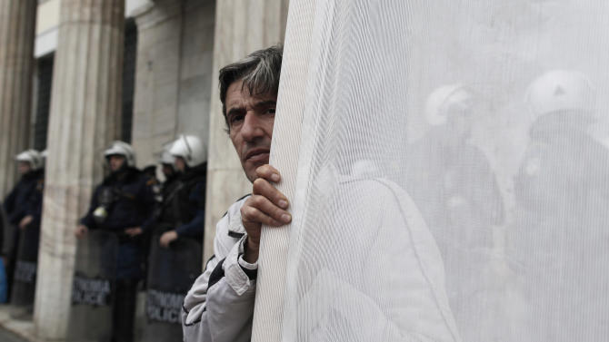 A protester holds a banner outside the Athens Town Hall, as riot police protect the entrance, during a demonstration by municipal employees on Monday, Nov. 19, 2012. Several hundred people took part in the protest, against government plans to place 2,000 civil servants on notice ahead of reassignment or potential dismissal. (AP Photo/Petros Giannakouris)