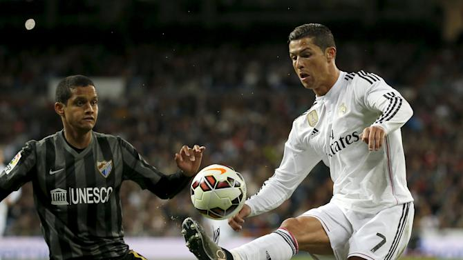 Real Madrid's Cristiano Ronaldo controls the ball next to Malaga's Roberto Rosales during their Spanish First Division soccer match at Santiago Bernabeu stadium in Madrid