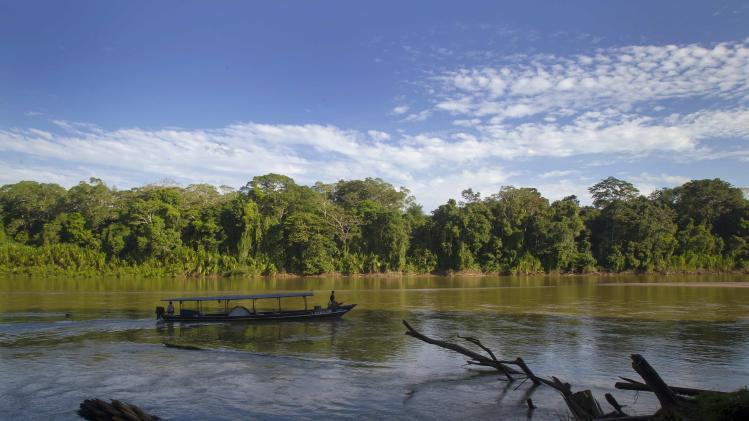 A boat navigates through the Manu river at the Manu National Park in Peru's southern Amazon region of Madre de Dios