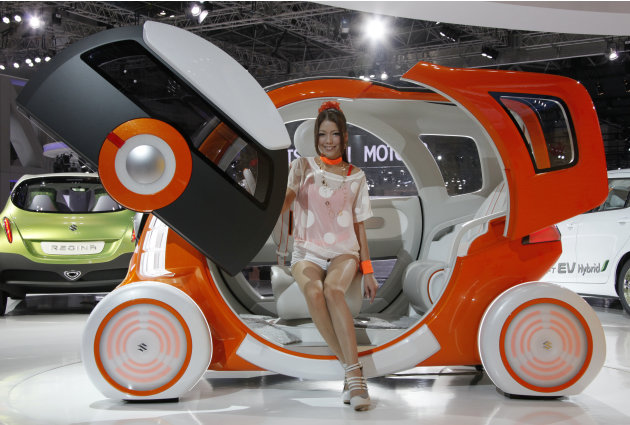 "A model sits on Suzuki Motor Corp.,'s concept car ""Q-Concept"" during the press preview of Tokyo Motor Show in Tokyo, Wednesday, Nov. 30, 2011. The Tokyo Motor Show opens to the public this weekend. (A"