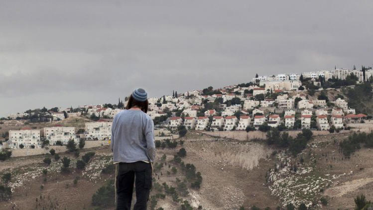FILE - In this Wednesday, Dec. 5, 2012 file photo A Jewish settler looks at the West bank settlement of Maaleh Adumim, from the E-1 area on the eastern outskirts of Jerusalem. Israel has proposed leaving intact dozens of Jewish settlements and military bases in the West Bank as part of a package to establish a Palestinian state in provisional borders, a Palestinian official told The Associated Press on Wednesday, Sept. 4, 2013, in the first detailed glimpse at recently relaunched peace talks. (AP Photo/Sebastian Scheiner, File)