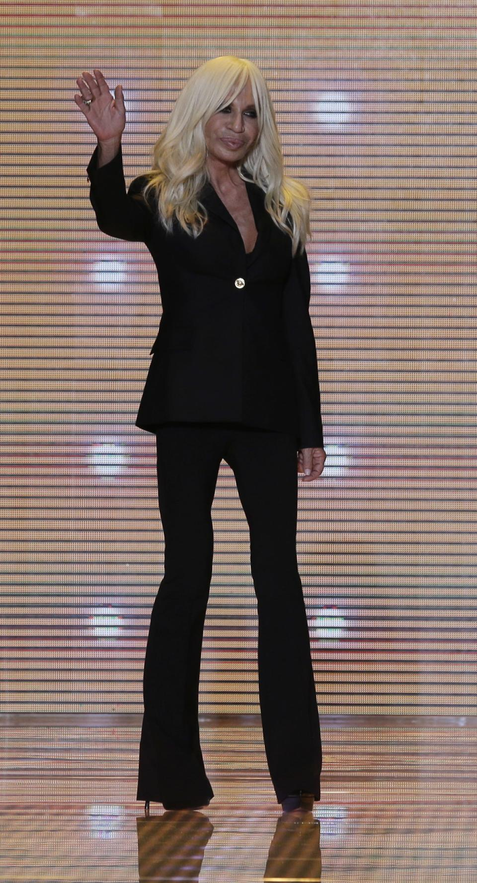 Italian fashion designer Donatella Versace waves at the end of the presentation of the Versace women's Fall-Winter 2012-2013 collection that was presented in Milan, Italy, Friday Sept. 21, 2012.(AP Photo/Luca Bruno)