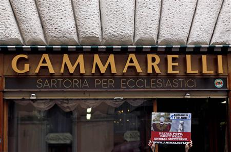 An Italian animal rights activist holds a sign in front of the Gammarelli tailor shop in Rome